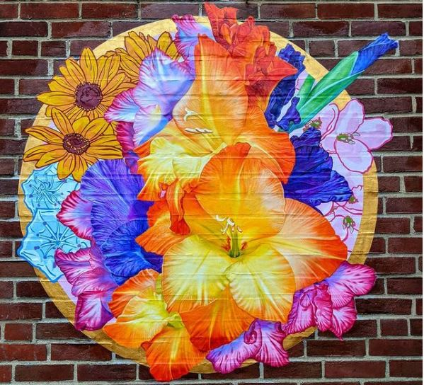 a circular garden mural with brightly coloured painted flowers