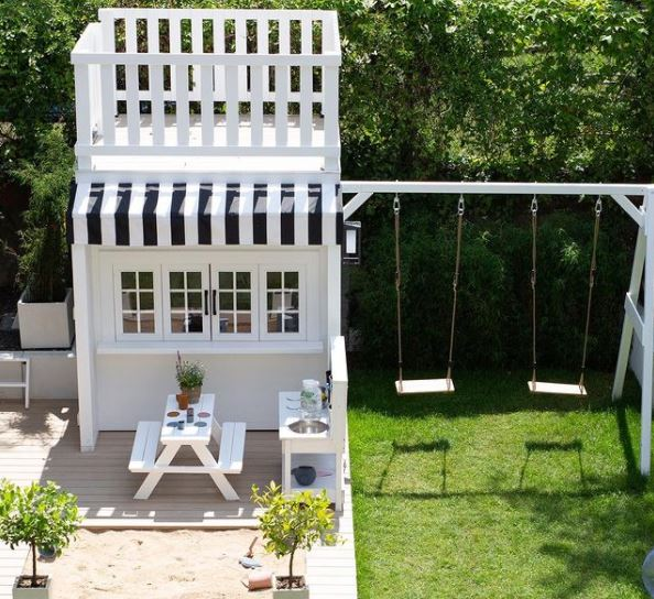 an elaborate playhouse designed to look like an ice-cream parlour, with an upper deck, picnic benches and striped awning