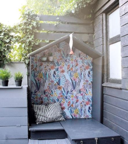 an open-faced garden playhouse with a colourfully painted back wall