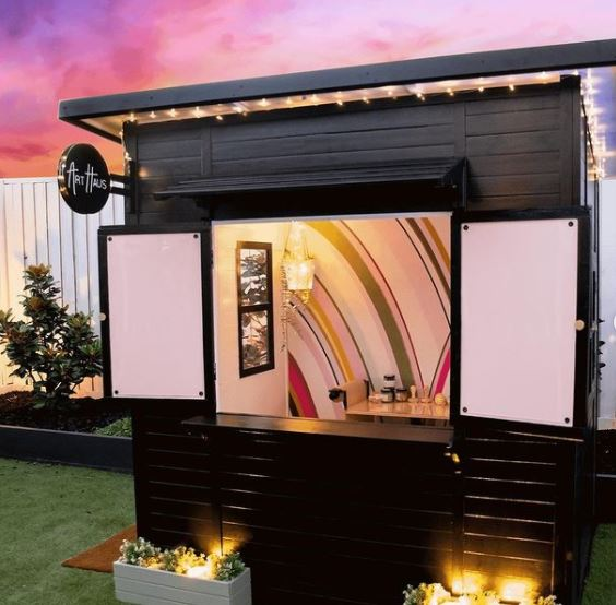 a glossy black shed with its window shutters open to reveal an artsy, movie-inspired interior