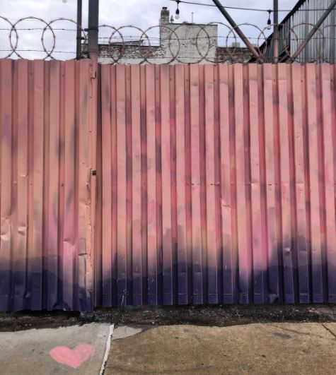 a fence that fades from shades of pink and coral to black and navy