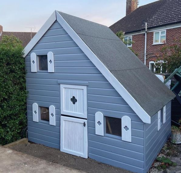 a wooden playhouse with an asymmetrical pitched roof, painted blue with a pretty white door and matching shutters