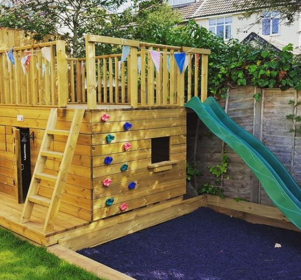 a big, boxy playhouse with a ladder and climbing wall up to a lookout-deck with a slide