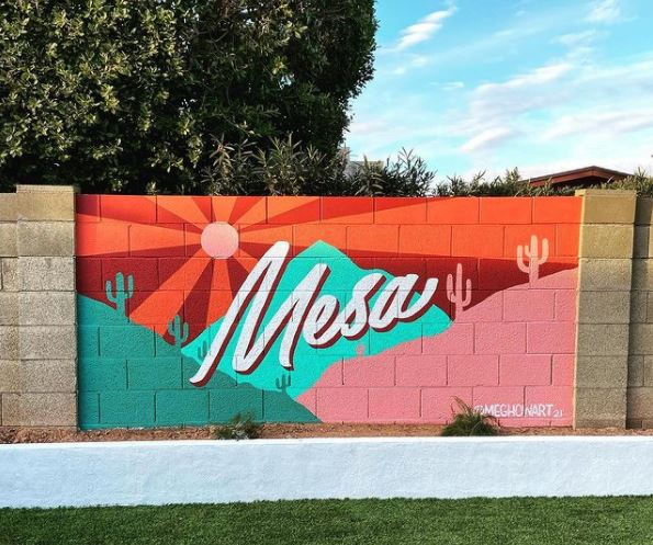 """a garden wall with a bright mural in warm colours that says """"Mesa"""" in the middle"""
