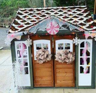 garden playhouse ideas with festive DIY decorations to make it look like a gingerbread house with icing and sweets
