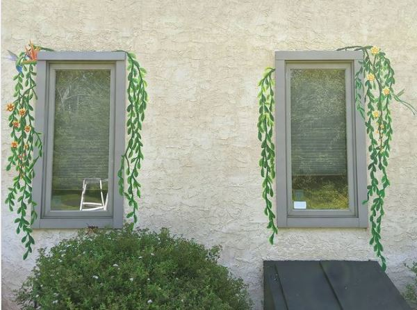 two outdoor windows with realistic leafy tendrils painted down the sides