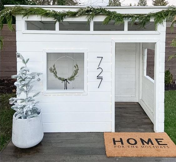 a white, mid-century style playhouse with wood floors and no front door