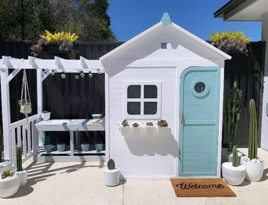 a bright white playhouse with a cheerful blue door. On the outside there is a window box, welcome mat and tiny pergola