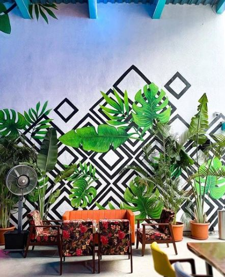 a seating area with a large mural of geometric shapes and lifelike plant leaves