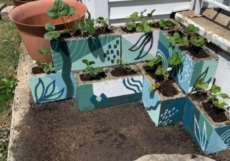 stacked up concrete breezeblocks being used as planters, all painted in various patterns and shades of blue