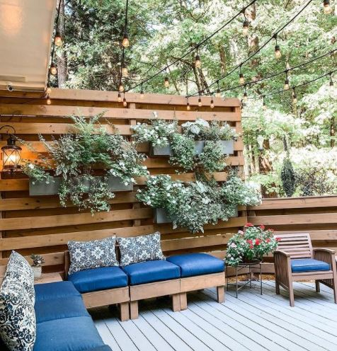 a garden deck area with taller fencing made from pallets behind the seating