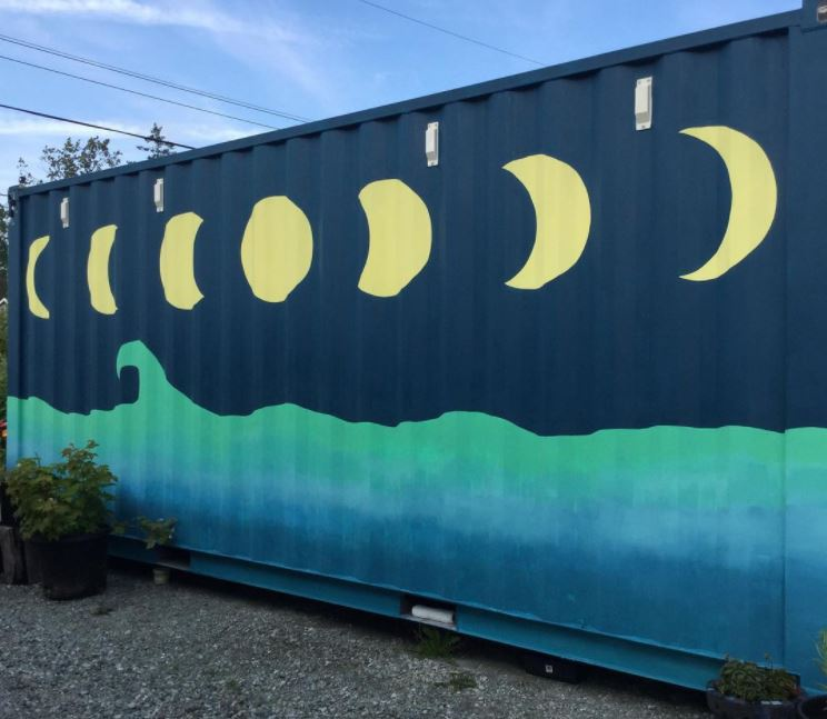 the side of a containers is painted with a turquoise sea and yellow moon phases