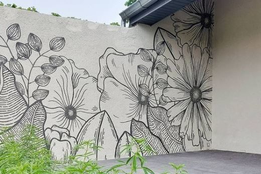 a black line drawing of flowers and leaves on a white garden wall