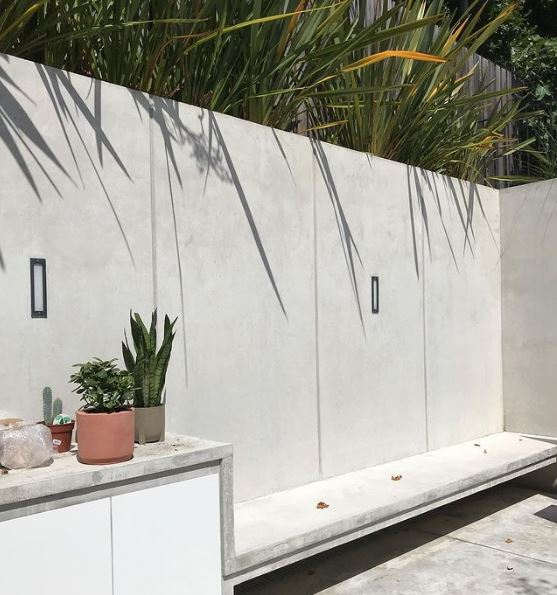 a concrete structure creates a seat, storage unit, wall and planter along the edge of a garden