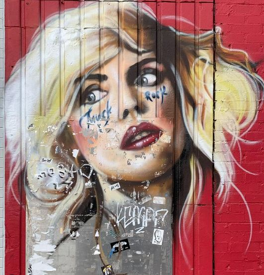 a portrait of Blondie painted in a graffiti style on a fence