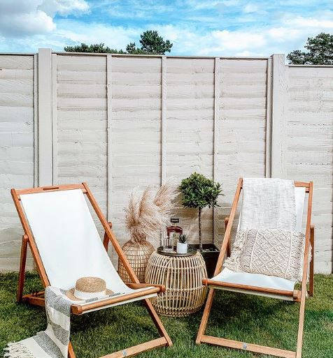 garden fencing ideas for painting: two deckchairs on an artificial lawn in front of a clean fence painted light grey