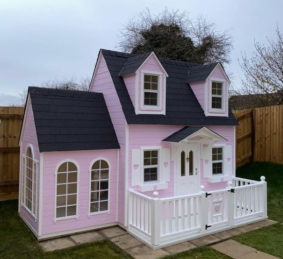 a huge pink playhouse with a front deck and what appears to be an extension with lots of windows