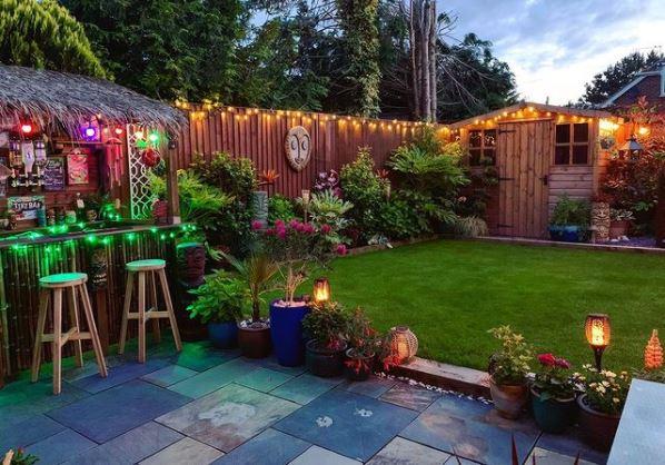 a UK garden with tiki garden ideas like a stone patio, wooden mask, exotic plants and tiki bar