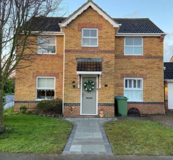 a large new-build home with a trim lawn and tidy garden path