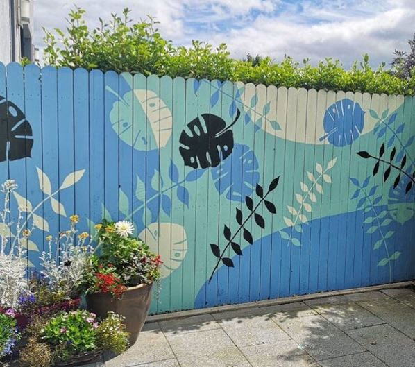 a garden fence painted with tropical leaf prints in shades of blue and turquoise