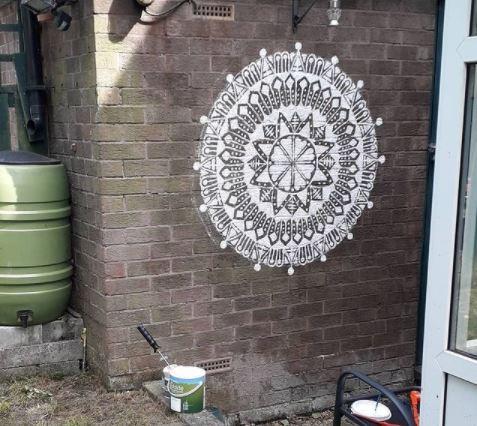an intricate mandala painted on a garden wall