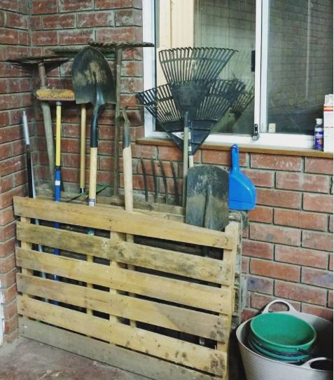 wooden pallets have been turned into storage bins for long garden tools like rakes and brooms