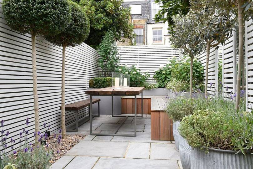 a small narrow garden with horizontally slatted fences and skinny trees