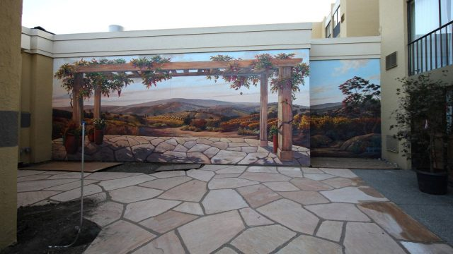 a trompe l-oeil painting that makes it look like a closed patio extends to the horizon