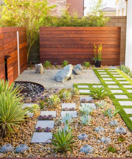 a small garden with a rockery, a strip of grass, a fountain and a tiny zen garden
