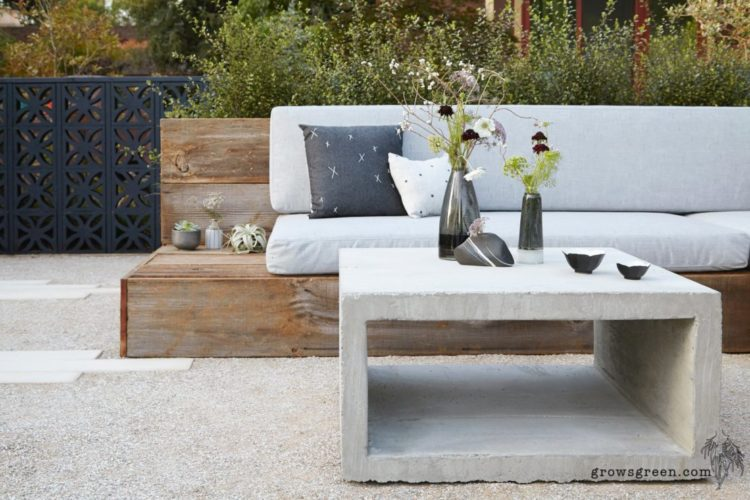 a hollow block of concrete used as a coffee table on a gravel patio, next to a simple wooden bench with grey padding