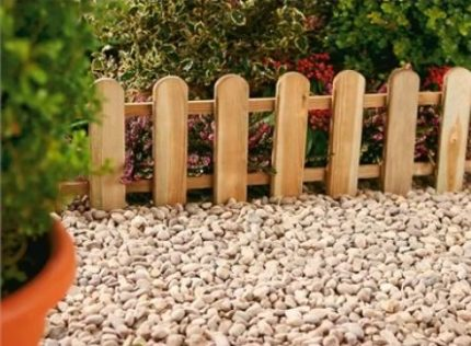 a miniature wooden picket fence used as garden edging between flower beds and gravel