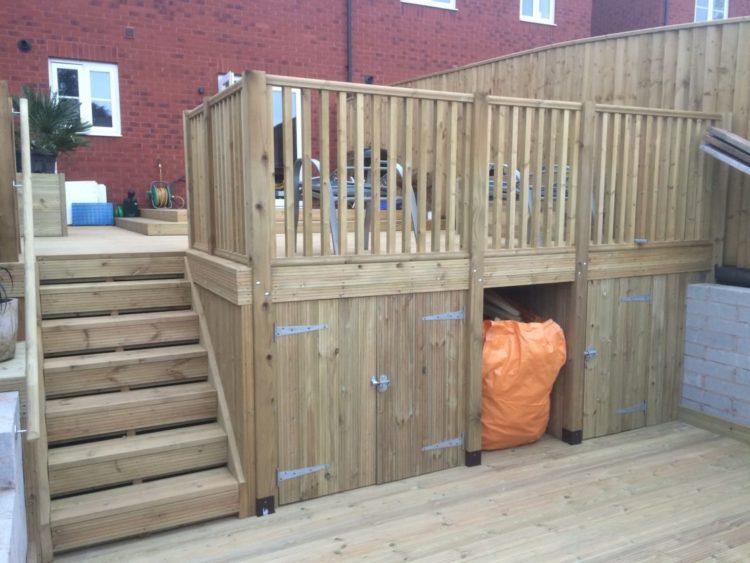 a raised deck with space to store garden equipment underneath