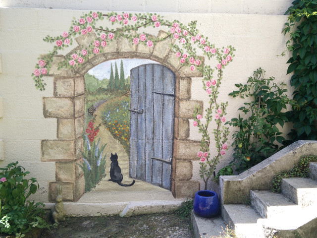 a painted doorway that appears to lead to a secret garden
