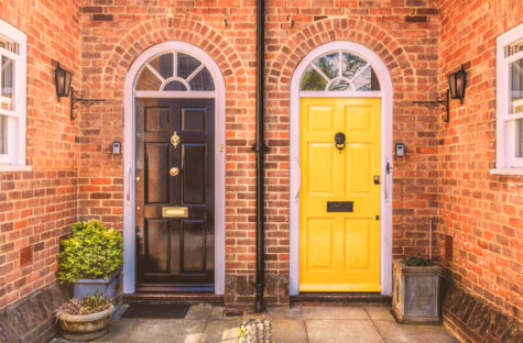 the entrances to two side-by-side terrace homes, with freshly painted doors and symmetrical lights, planters and brackets for hanging baskets.