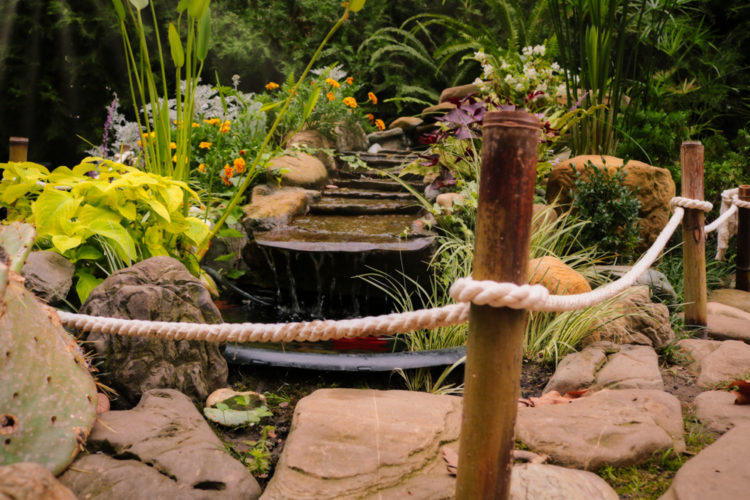 a garden water feature behind a decorative rope fence