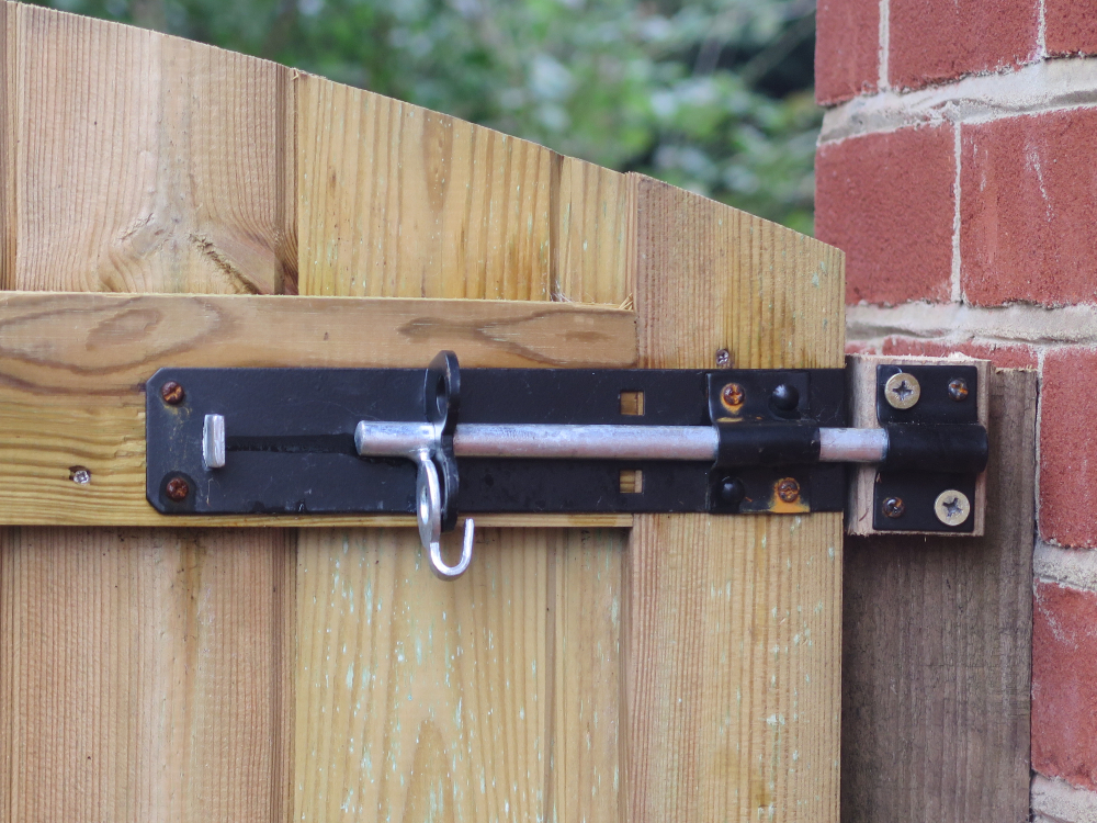 a long metal bolt securing a wooden gate into a brick wall