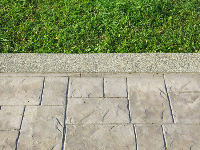 close up of a stamped concrete path next to a crisp lawn edge