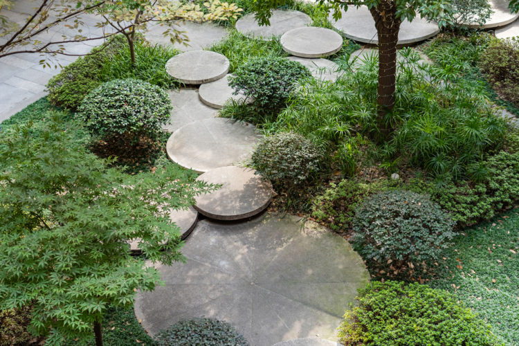 round concrete stepping stones overlapping through circular shrubs and flower beds