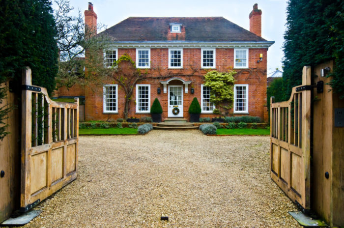 double gates opening into a long gravel driveway leading to a large country house