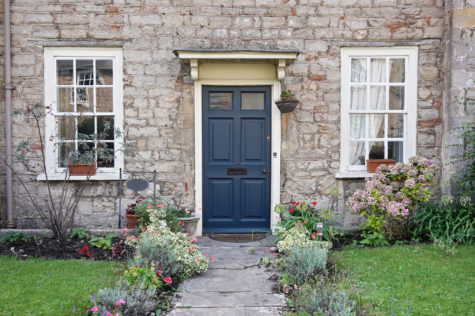 the front of a stone house with a blue front door, mowed lawn and neat flowers along the path