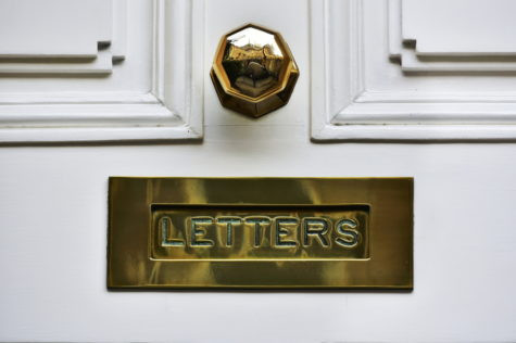 a close-up of a polished letterbox and doorknob in a traditional style
