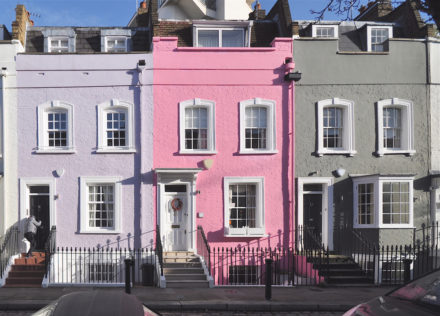 a row of terraced homes in clean pastel colours