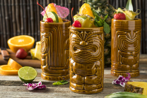 three novelty ceramic tiki mugs shaped like wood carvings are filled with exotic fruit drinks