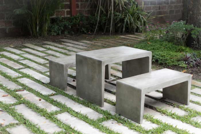 a simple concrete table and matching bench seats in a garden with concrete paving stones that have grass growing between