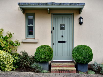 the entrance to a home with neat box shrubs either side of a grey-green door. There is an exterior light on the wall.