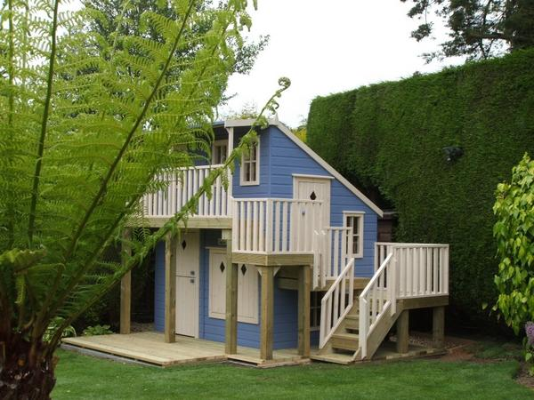a two-storey playhouse with a set of wooden stairs leading to a separate door on the second level