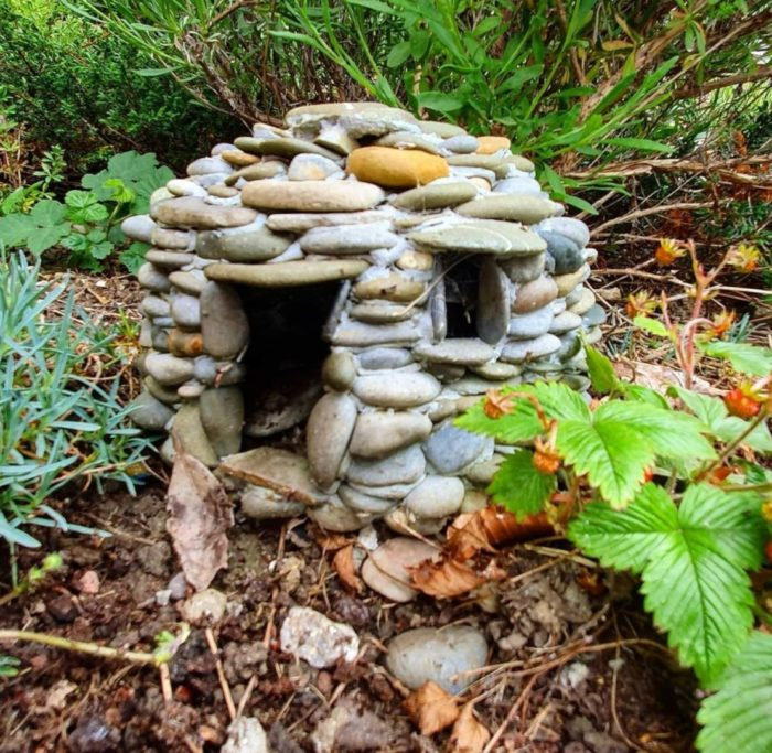 a tiny house made from pebbles nestled in the undergrowth of a garden