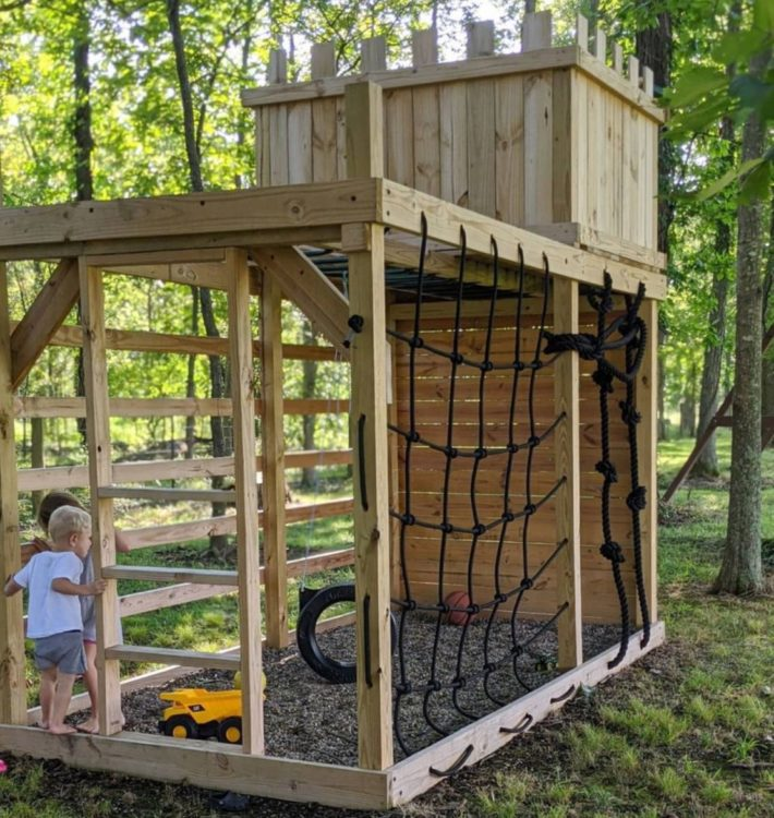 a treehouse with obstacle features like a climbing net and tyre swing