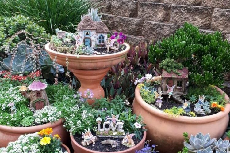 a garden with lots of pots, some of which have little fairy houses and decorations in