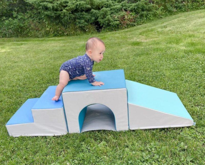 an infant crawling across a soft-play bridge outside